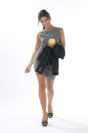 Full length healthy young business executive woman, on white, looking at camera, walking holding an apple.