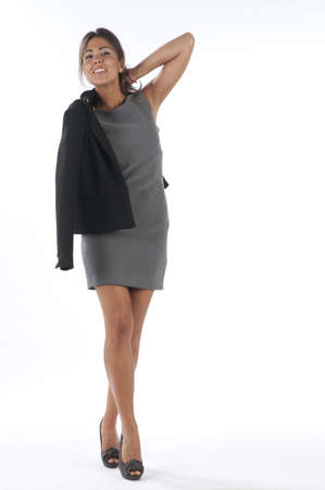 Full length Self confident young business executive woman, on white, puting on her jacket. Stock Photo