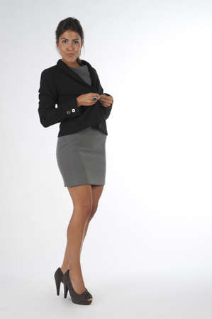 Young business executive woman, on white, bottoning her jacket. Stock Photo - 14429743