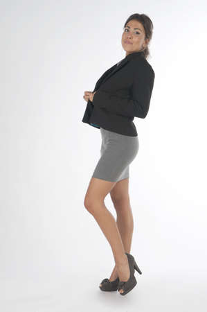 Young business executive woman, on white, bottoning her jacket.