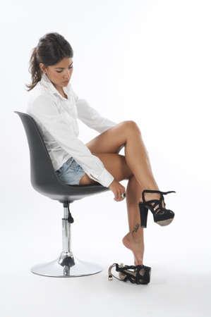 mujeres sentadas: Chica seria joven en blanco, tratando en el par de zapatos