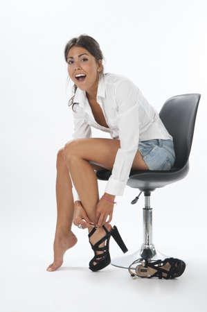 mujeres sentadas: Ni�a en blanco, riendo al intentar en un par de zapatos