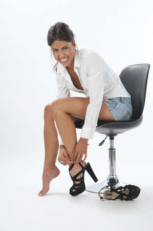 Young girl on white, smiling while trying on pair of shoes Stock Photo