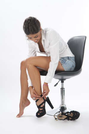 Young girl on white, trying on pair of shoes Stock Photo