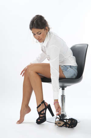 Young girl on white, trying on pair of shoes photo