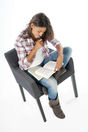 Young girl student, on white, wearing jeans and shirt, sitting on sofa reading book  Stock Photo