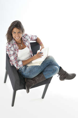 Happy young girl student, on white, wearing casual clothing, sitting on sofa reading book.