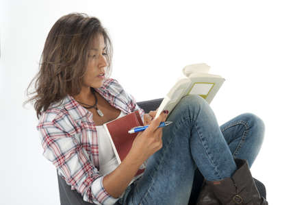 Happy young girl student, on white, wearing casual clothing, sitting on sofa reading book Stock Photo - 14938101