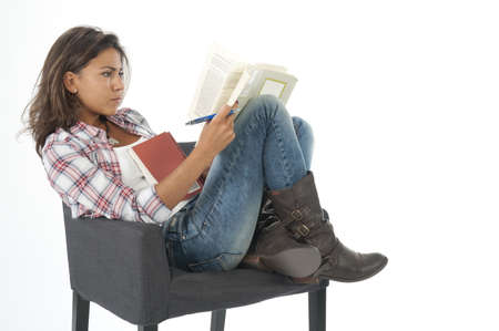 Serious, concentrated young girl student, on white, wearing jeans and shirt, sitting on sofa reading book