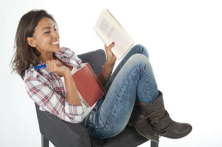Happy and smiling young girl student, on white, wearing jeans and shirt, sitting on sofa reading book