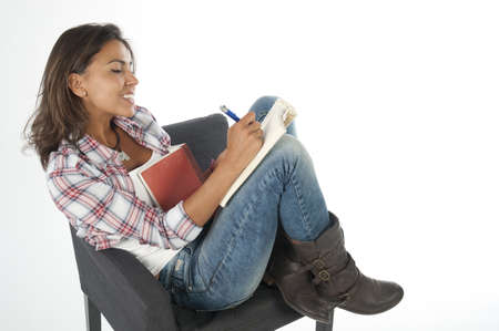 Young girl student, on white, wearing jeans and shirt, sitting on sofa reading book Stock Photo - 14938098