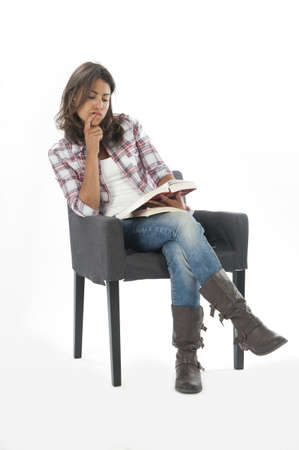 Concentrated, young girl student reading book, on white, wearing jeans and shirt, sitting on sofa Stock Photo - 14938081