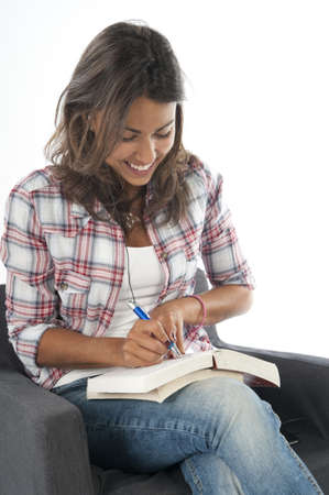 Happy young girl student writing notes, on white, wearing jeans and shirt, sitting on sofa.
