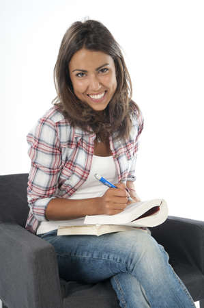 Portrait of happy smiling young girl student reading book, sitting on sofa on white, wearing jeans and shirt