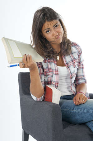 Bored young girl student, sitting on sofa reading book, on white, wearing jeans and shirt
