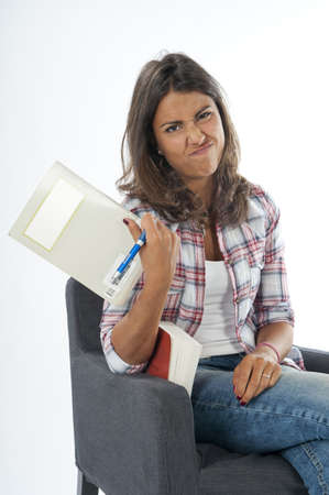 Bored young girl student, sitting on sofa reading book, on white, wearing jeans and shirt  Stock Photo - 14938104
