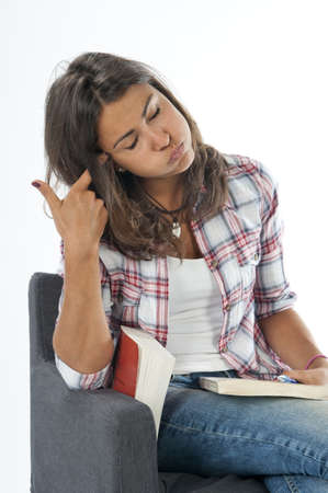 Bored to death, young girl student, sitting on sofa reading book, on white, wearing jeans and shirt  Stock Photo