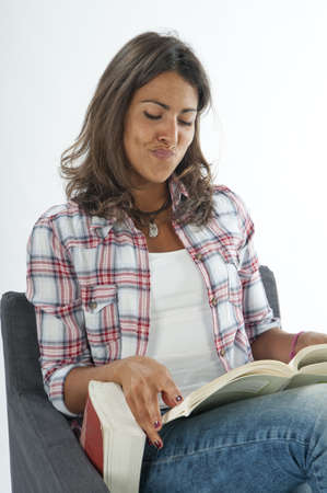 Satisfied young girl student, sitting on sofa reading book, on white, wearing jeans and shirt Stock Photo - 14938110