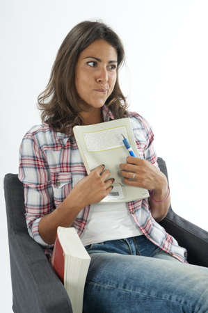 Young girl student, memorizing a book, sitting on sofa on white, wearing jeans and shirt.