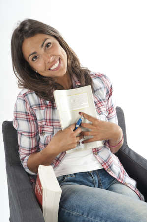 Young girl student sitting on sofa, holding a book, on white, wearing jeans and shirt  Stock Photo