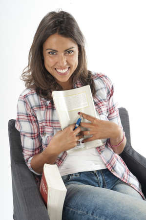 Portrait of happy smiling young girl student, sitting on sofa, holding a book, on white, wearing jeans and shirt