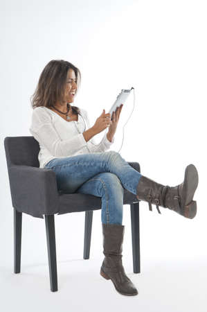 Happy young girl wearing casual clothing, on white, sitting on sofa holding tablet PC. Stock Photo - 14591103