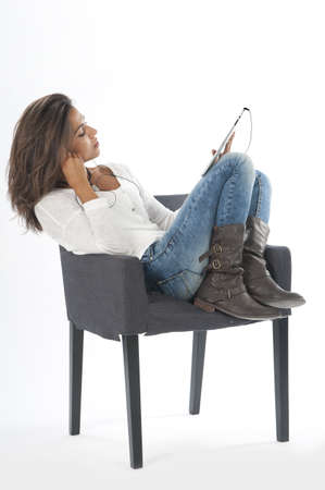Happy young girl wearing casual clothing, on white, sitting on sofa holding tablet PC. Stock Photo
