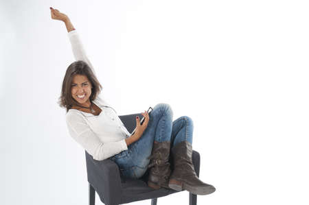 Happy young girl with her arm up, wearing casual clothing, on white, sitting on sofa holding tablet PC with hands up.
