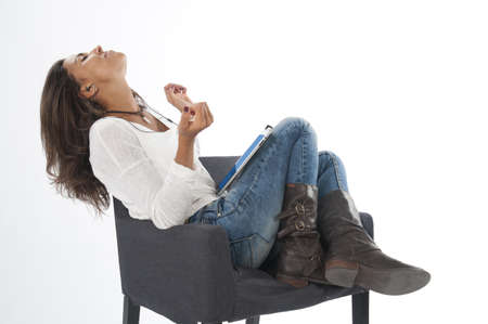 Happy young girl wearing casual clothing, on white, sitting on sofa holding tablet PC, listening to music.