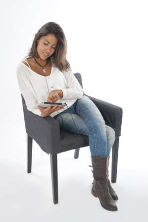 Concentrated young girl wearing casual clothing, on white, sitting on sofa holding tablet PC. Stock Photo