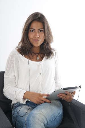Thoughtful young girl wearing casual clothing, on white, sitting on sofa holding tablet PC. Stock Photo