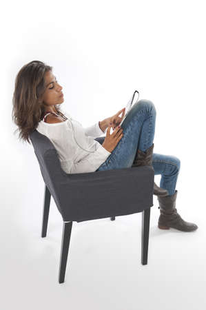 Serious young girl wearing casual clothing, on white, sitting on sofa holding tablet PC. Stock Photo