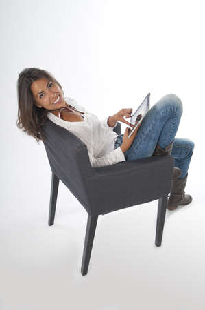 Happy young girl wearing casual clothing, on white, sitting on sofa holding tablet PC. Stock Photo - 14591110