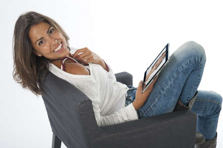 Happy young girl wearing casual clothing, on white, enjoying photos on tablet PC. Stock Photo
