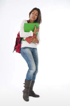 Young bussy girl student, on white, wearing jeans and t-shirt, holding notebooks. Stock Photo - 14590928
