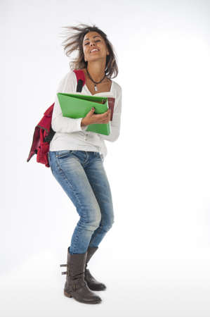 Full size portrait of happy young girl student, on white, wearing jeans and t-shirt, holding notebooks. Stock Photo