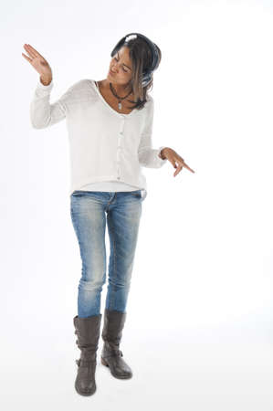 Full length portrait of young girl, on white, wearing casual clothing, enjoying music with head phones.