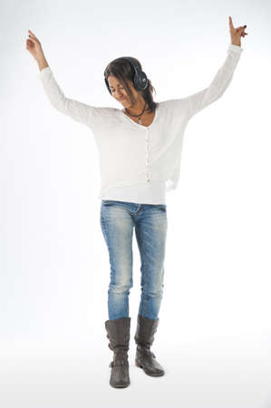 Full length portrait of young girl, on white, wearing casual clothing, enjoying music with hands up and head phones