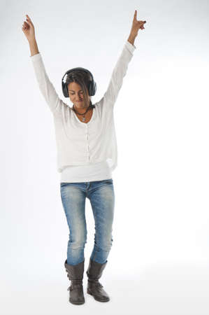 Full length portrait of young girl, on white, wearing casual clothing, enjoying music with hands up and head phones  photo