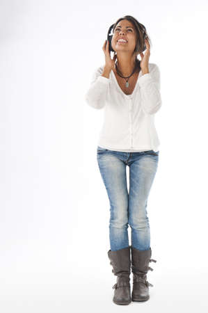 Full length portrait of young girl with casual clothing, on white, shouting with open mouth and hands on head phones, enjoying music