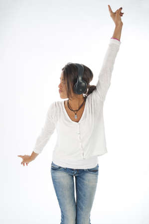 Three quarter length portrait of young girl with casual clothing, on white,  enjoying music with headphones and hands up.