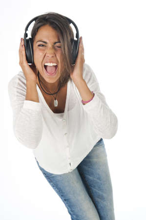 Happy young female adult with headphones, enjoying singing with open mouth and dancing, while listening to music. Stock Photo