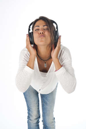 Three quarter length portrait of young girl with casual clothing, on white,  enjoying music with hands on headphones blowing a kiss