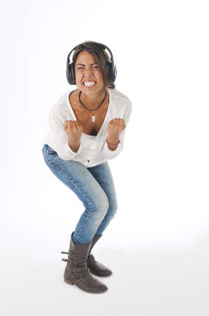 Happy young female adult with headphones, enjoying singing with open mouth and dancing, while listening to music