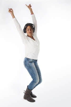 Full length portrait of young woman with casual clothing and headphones, on white background,  enjoying music dancing with hands up.