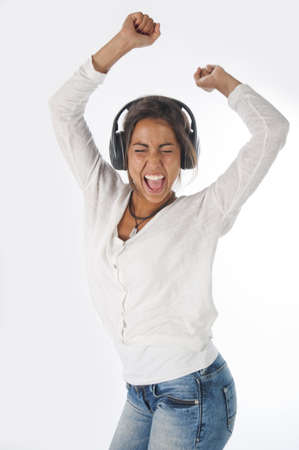 Happy young female adult with headphones, enjoying singing with open mouth and dancing with hands up, while listening to music