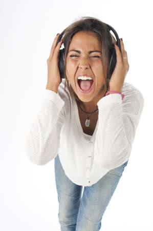 Three quarters portrait of happy young female adult with headphones, enjoying listening to music while singing enthusiastically with open mouth. Stock Photo