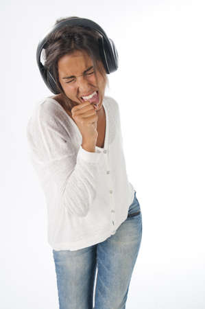 Three quarters length portrait of young woman with casual clothing and headphones, on white background,  enjoying music singing and dancing