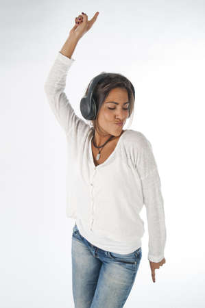 Three quarter length portrait of young woman with casual clothing, on white background,  enjoying music with headphones and dancing with hands up. Stock Photo
