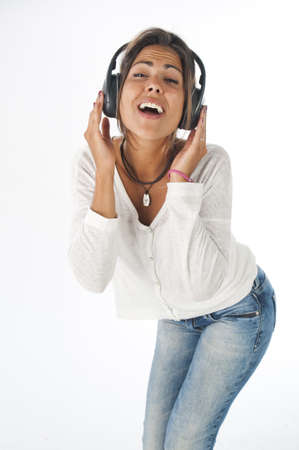 Happy young female adult with headphones, enjoying singing with open mouth and dancing, while listening to music. photo